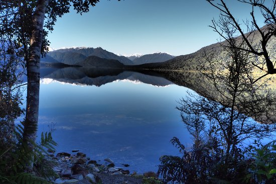 Glassy waters looking out over Lake Kaniere, on our West Coast Wilderness & Beyond Trail. It lies 30 kilometres southeast of Hokitika and drains into the Tasman Sea via the Kaniere and Hokitika rivers. beautiful spot for a picnic lunch!