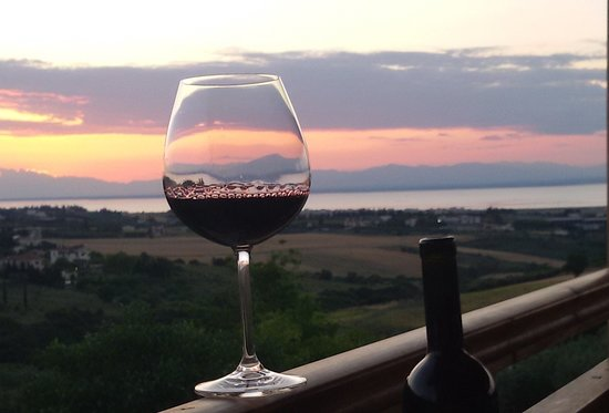 """Trilofo, Griekenland: having a glass from our summer red """"SYMPHONY"""" a blend consisting xinomavro grapes, syrah and agiorgitiko, at our balcony at sunset"""