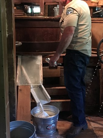 Bristol, IN: Flour being made and collected in a bucket at the park ranger's feet at Bonneyville Mills.