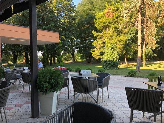 Foto vom Parkplatz und Aussicht vom Kaffee/Restaurant auf den kleinen Park.