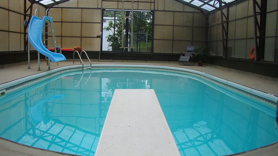 Indoor 18' x 35' heated pool with slide and comfy lounging chairs.