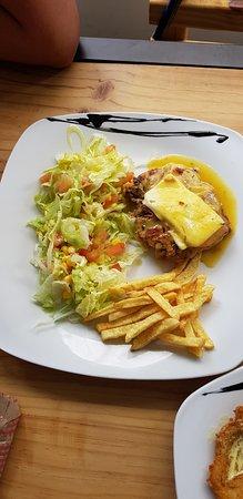 hamburguesa casera con queso acompañada con ensalada fresca