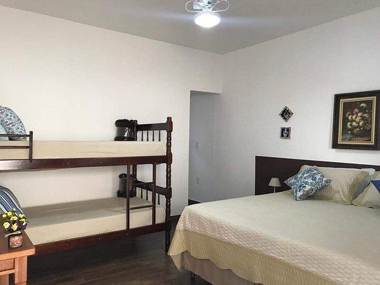 """SUÍTE FLAMBOYANT - As nossas suítes comportam até 4 hóspedes nas seguintes configurações: 1 cama box de casal Queen+ e 1 beliche com 2 lugares ou; 2 camas box de solteiro e 1 beliche com 2 lugares; Todas as suítes possuem TV LED de 32"""" com SKY* (* pacote básico), mesa de trabalho, ventilador de teto, guarda roupa e banheiro privativo com ducha turbo."""