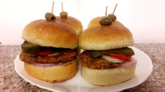 Our special KIRAN burger. The buns are made in our bakery and filled with a home made lentil burger, fresh vegetables and pickled gherkins.