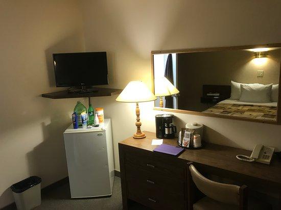 Bureau de travail, TV écran plat, cafetière et mini-frigo.