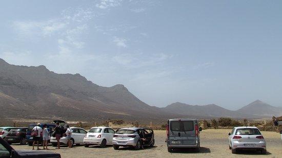 Aparcamiento en la playa de Cofete con el cementerio y las montañas de Jandía al fondo