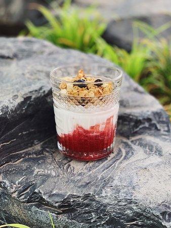 Нежный йогурт с хрустящими мюсли подается со свежей голубикой, бананом и клубничным соусом.