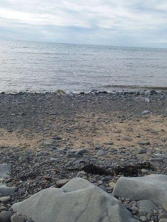 Aberaeron, UK: North Beach è una  spiaggia di ghiaia e roccia  usata regolarmente da pescatori, velisti e surfisti, noi abbiamo passeggiato  sul camminamento asfaltato.