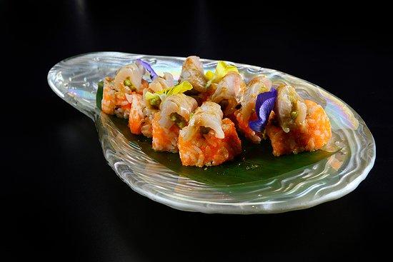 Hamachi Maki:Roll di ricciola, cipollotto, masago e spicy con all'esterno ricciola marinata e fiammeggiata, avocado, masago, coriandolo e salsa chili