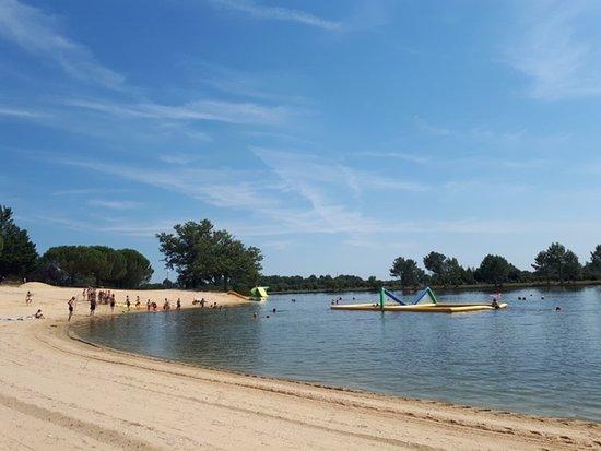 Lac de baignade contrôlé par ARS  et alimenté par des sources avec sa plage de sable et ses pins parasol