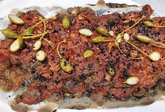 Pinsa Nera con Moscardini, Fiori di Capperi, Olive e Pomodorino