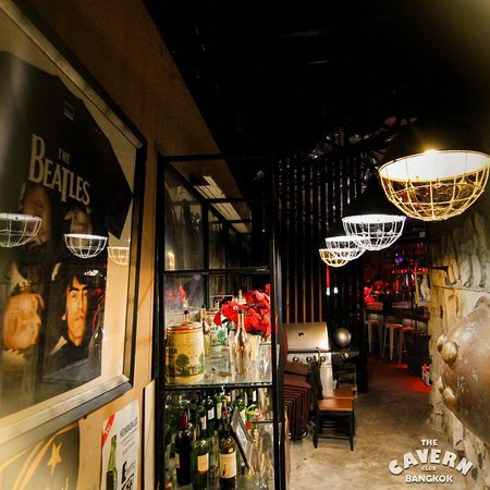 """The Cavern Club Bangkok: The bar's exterior is a combination of rock and wood, with a huge """"Cavern Club"""" sign front and center. It's a classic formula—just think The Rock Pub or Hard Rock Café. Inside is a pretty typical restaurant setting, glammed up with framed pictures of The Beatles and the owner's personal collection of retro memorabilia. The stage sits to one side of the room illuminated by red, blue and green lights.      """