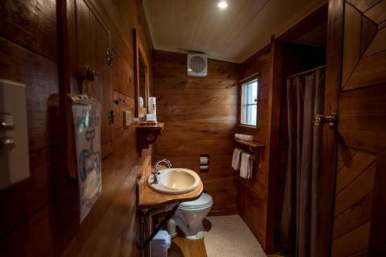 wood lined bathroom, cozy with fluffy soft white towels and toiletries provided.