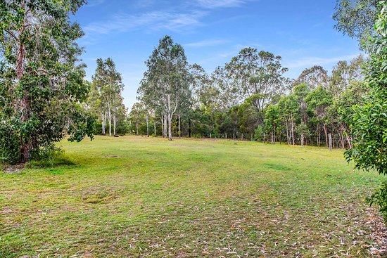 A typical camping spot at Fraser Coast RV Park, plenty of sun and shade and grass, lots of privacy