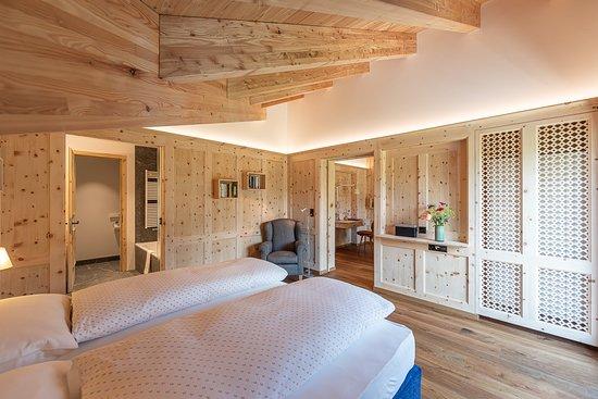 Hotel Chesa Randolina: Panorama Suite mit Balkon zum Silsersee. Zwei separate Badezimmer mit Dusche und Badewanne, DuschWC, Wohnraum und separatem Schlafzimmer, alles in Arvenholz