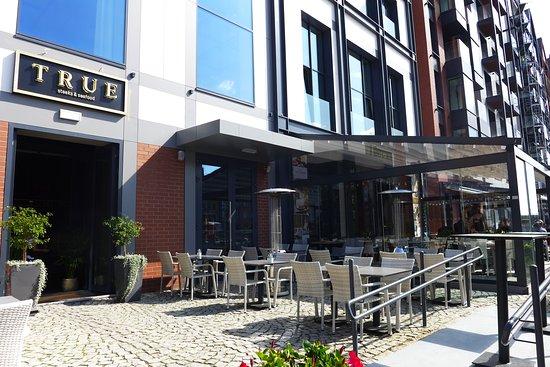 TRUE Steaks & Seafood RESTAURANT: Die Eingang des Restaurants findet man im Erdgeschoss eines modernen Wohnhauses.