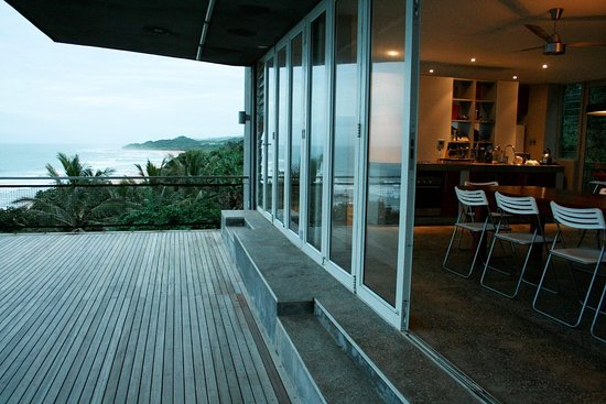 The vast front deck off the open plan living area overlooking the ocean to the east and the indigenous forest below.  Four ensuite bedrooms below and above also overlook the sea