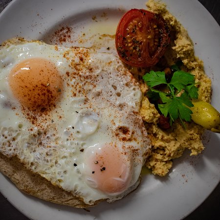 Pitta breakfast - a warm pitta bread topped with two free range eggs and served with homemade hummus, tomato and shipman pepper.