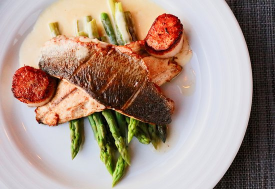 Pan fried fillets of sea bass, with fresh asparagus, scallops, and a white wine scallop reduction
