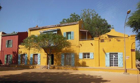 Podor, Senegal: La façade principale avec la partie principale, e, jaune, et l'aile Sud de la bibliothèque et de la chambre/studio du Terrier rouge.