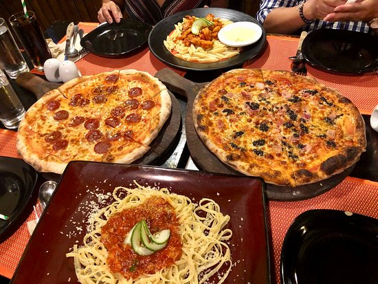 Shows a table of pizza and pasta dishes at Altrove Pizza restaurant