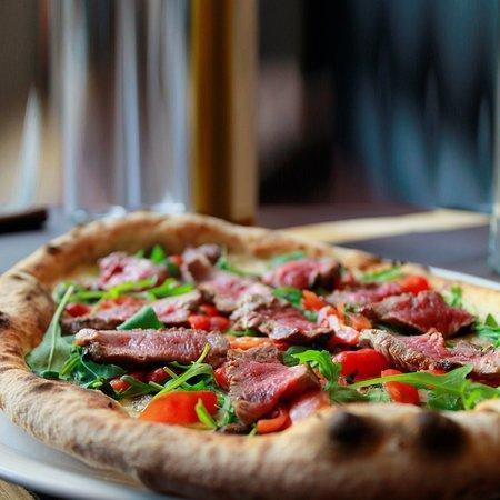 Pizza gourmet dei nostri chef Meat Steak con carne alla brace di manzo uruguaiano, pomodorino condito, rucola e fior di latte, al Flame'n Co.