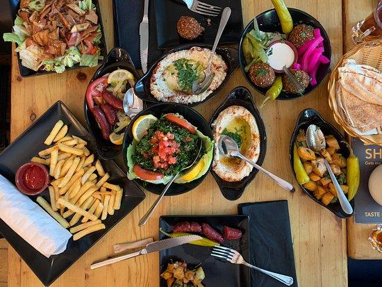 Chiswick, UK: Da sinistra: insalata fattoush, panino shawarma con pollo e patatine, moutabal, tabouleh, felafel, batata harra, Sujuk