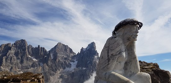 Passo Rolle, إيطاليا: Il Cristo Pensante.  Sullo sfondo le Pale di San Martino.  La prima cima a destra è il Cimon della Pala 3184, secondo alla cima principale,  la successiva verso sinistra la Vezzana 3192.