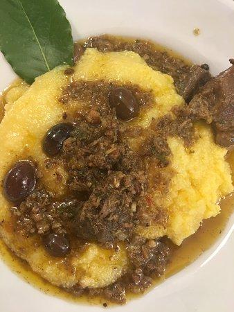 Spezzatino di cinghiale con le olive servito con polenta