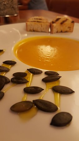 Kürbiscrem-Suppe mit Kokosmilch, Safran-Balsamico, Geröstete-Kürbiskerne und Kräuter-brot.