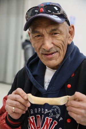 """Pond Inlet, Canada: Chasseur Inuit montrant ses """"lunettes de soleil"""" taillées dans un os de caribou"""