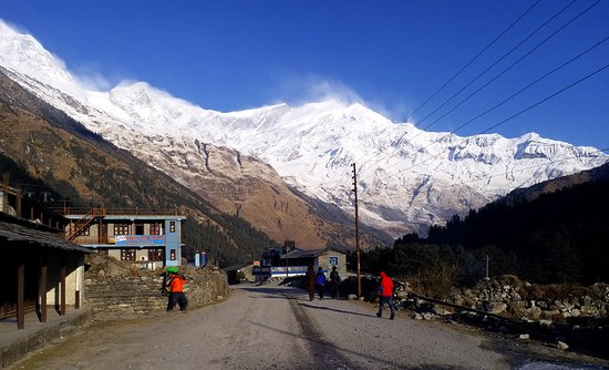Lete, Nepal: Trail to Annapurna Circuit Trek with remote lively village of Kalopani in foreground. The steaming mountain in background in Mt. Dhaulagiri in the left and Mt. Takucha peak in the Right of picture.