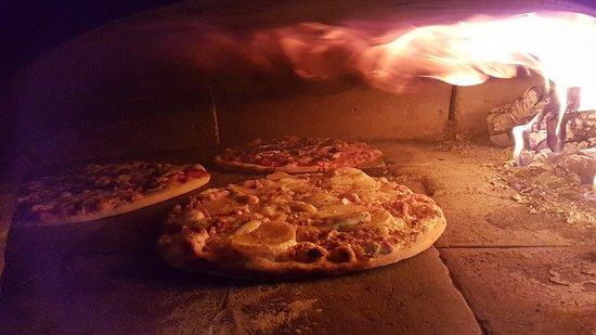 Nos pizzas et tartes flambées sont cuitent au véritable feu de bois devant vous