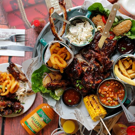 Ranchers Feast - A whole rack of hickory smoked ribs, chicken wings, stuffed jalapeños, ballyhoo prawns, corn on the cob, creamy coleslaw, ranch beans & fries