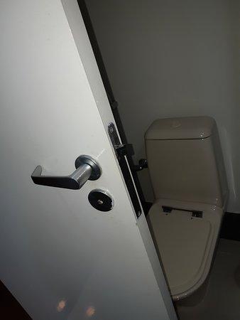 Toilet tucked in behind the door.