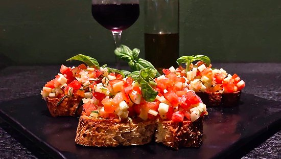 Classic Bruschetta Fresh crusty bread, rubbed with garlic cloves, drizzled with olive oil, and sprinkled with salt and pepper, topped with fresh chopped tomatoes, cucumber, and basil.