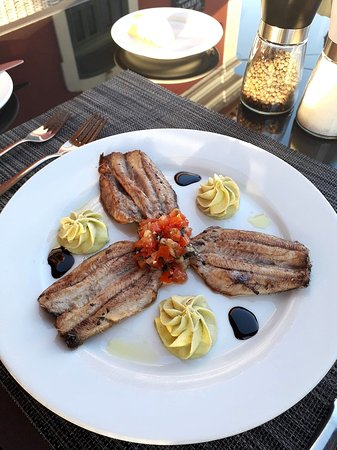 Seared sardine fillets with avocado cream, tomato salsa, balsamic reduction and a gentle touch of curry oil.