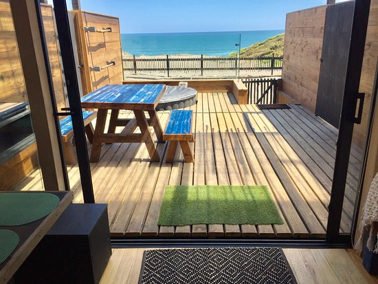 Boca Pupuya, Chile: Foto de la terraza desde el interior de 25 Nudos Lodge hacia la playa, se ve la zona de parrilla , mesa de terraza y jacuzzi con una increíble vista al mar.