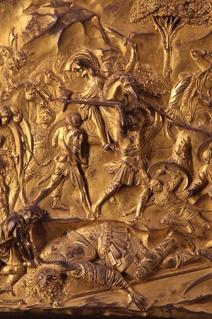Detail from Ghiberti's Gates of Paradise. This panel shows David cutting off Goliath's head after he has felled him with his slingshot.