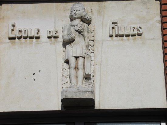 Haut-relief signalant de l'entrée des filles représentant une écolière