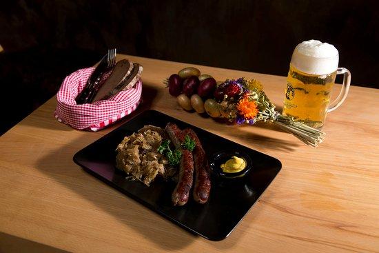 Marktheidenfeld, Duitsland: Leckere Wildbratwürtst mit hausgemachtem Sauerkraut fränkischem Schwarzbrot und einem frisch gezapftem Bier vom Fass