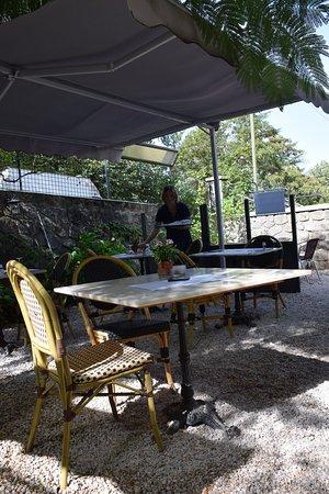 Sur la terrasse extérieure de jour. On aperçoit la patronne préparant ses tables.