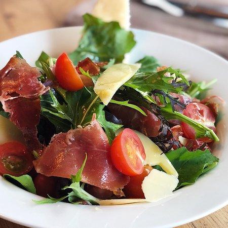 Ensalada mediterránea: mezclum de hojas verdes, rúcula, albahaca, tomate, olivas, parmesano, pimientos rojos asados, berenjena, almendras y jamón crudo..