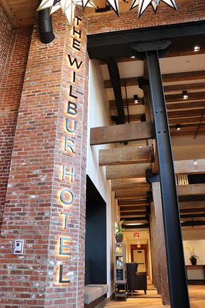 Lobby area of The Wilbur Hotel with original brick, steel and wood beams, to show the history of this building.