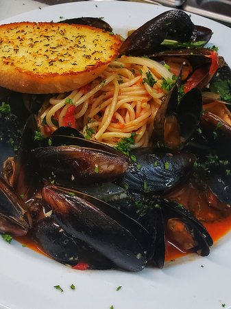 Mussels steamed with saffron tomato broth with fresh basil, spaghetti and garlic bread