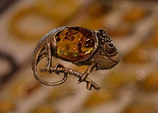 Bursztynowo-srebrna zawieszka w kształcie kameleona.