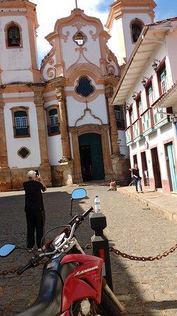 Igreja, com um prédio lateral e suas sacadas típicas.