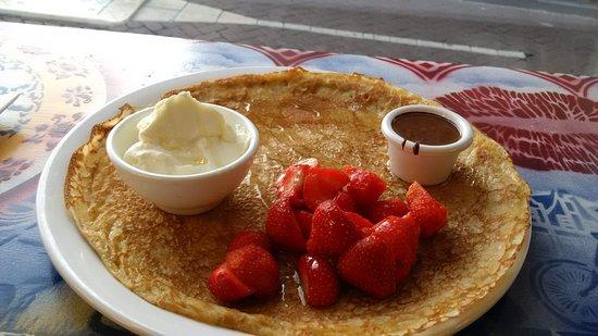 Dutch pancake with lemon cream, strawberries and a side of chocolate sauce.