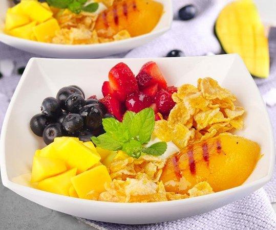 Coconut bowl, yogurt tipo griego con coco, servido con cereal, frutas de la estación y durazno al grill.