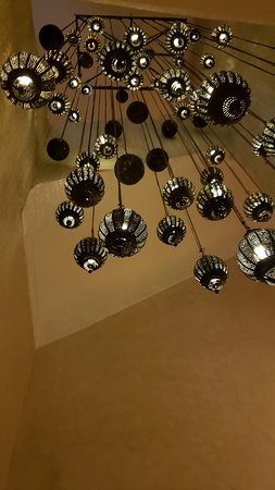 Beautiful light fixture hanging in the staircase to the dining area